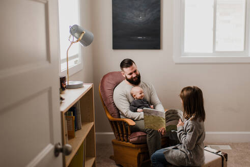Girl in living room showing book to father and baby brother - ISF22983