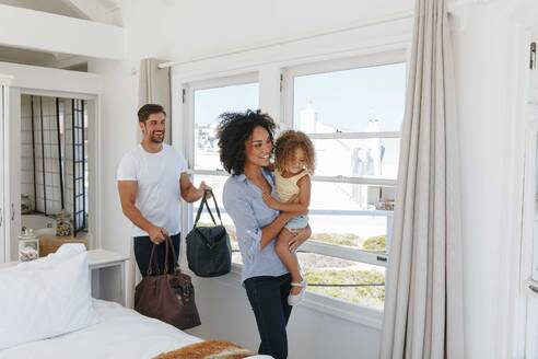 Couple and daughter leaving bedroom in beach house - ISF23124