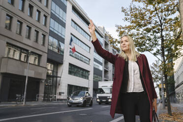 Blond businesswoman in the city hailing a taxi - AHSF01356