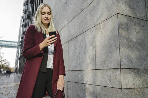 Blond businesswoman using smartphone in the background modern building - AHSF01359