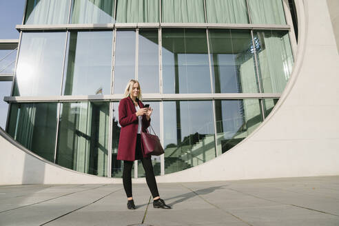 Blond businesswoman using smartphone in the background modern building - AHSF01362