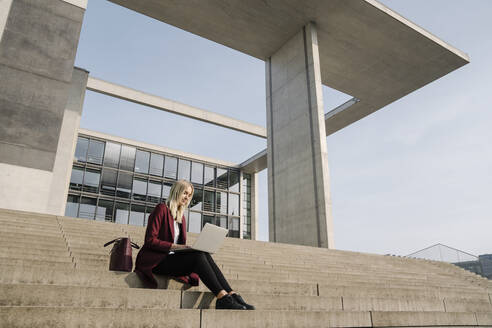 Blond businesswoman with laptop in the background of modern office building - AHSF01368