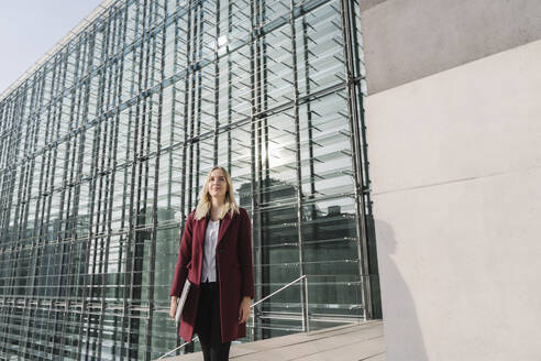 Blond businesswoman with laptop in the background of modern office building - AHSF01371
