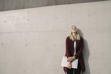 Blond businesswoman with laptop leaning on wall with closed eyes - AHSF01374