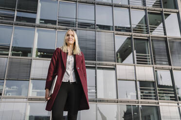 Blond businesswoman with laptop in the background of modern office building - AHSF01377