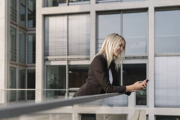 Blond businesswoman using smartphone in the background modern building - AHSF01383