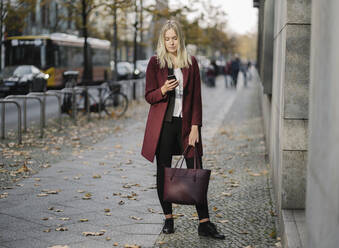 Blond businesswoman using smartphone in the city - AHSF01392