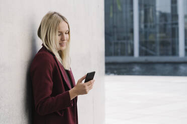 Blond businesswoman using smartphone, leaning on a wall, looking down - AHSF01395