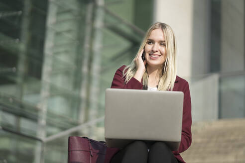 Blond businesswoman using laptop and phoning, sitting on steps - AHSF01401