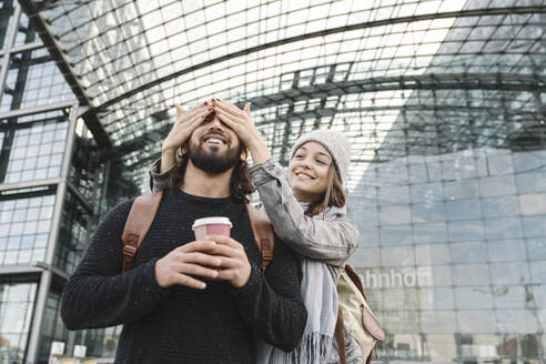 Happy young woman surprising boyfriend at the central station, Berlin, Germany - AHSF01411