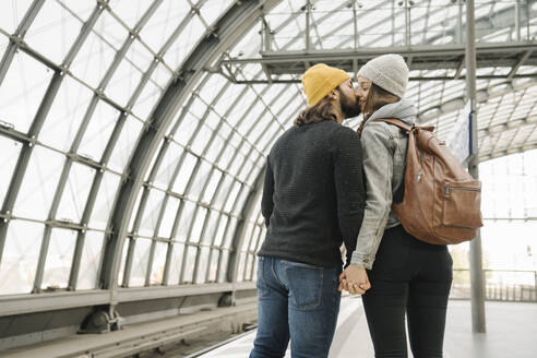 Young couple kissing at the station platform, Berlin, Germany - AHSF01435