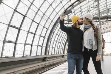 Young couple kissing and taking a selfie at the station platform, Berlin, Germany - AHSF01438