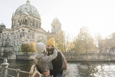 Young couple embracing with Berlin Cathedral in background, Berlin, Germany - AHSF01468