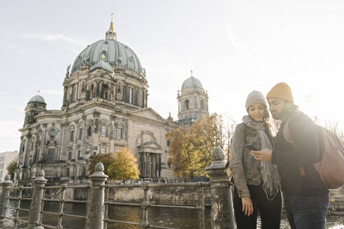 Germany, Berlin, Couple using smartphone and earphones in the city - AHSF01471