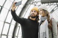 Happy young couple taking a selfie at the station platform, Berlin, Germany - AHSF01492