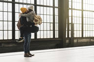 Affectionate young couple kissing at the station platform, Berlin, Germany - AHSF01501