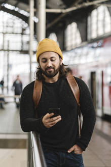 Young man using smartphone at the station platform, Berlin, Germany - AHSF01504