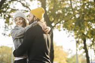 Happy young couple embracing in a city park, Berlin, Germany - AHSF01510