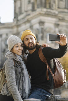 Young couple taking a selfie with Berlin Cathedral in background, Berlin, Germany - AHSF01516