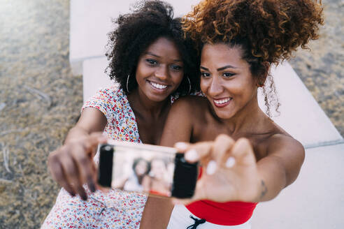 Young women smiling and making a selfie with their smart phone in a park, focus on background - MPPF00316