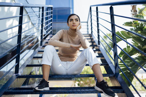 Young woman sitting on exterior stairs - JSMF01370