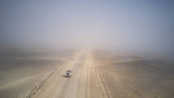 Drone view of a 4x4 in the foggy desert, Namibia - VEGF00907