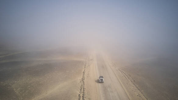 Drone view of a 4x4 in the foggy desert, Namibia - VEGF00910