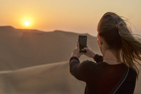 Woman taking a smartphone picture in the desert at sunset, Dune 7, Walvis Bay, Namibia - VEGF00958