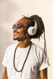 Portrait of mature man with dreadlocks and headphones, listening music and looking sideways - TCF06209