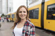 Smiling woman in the city with a tram in the background, Berlin, Germany - WPEF02294
