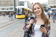Portrait of smiling woman in the city with a tram in the background, Berlin, Germany - WPEF02300