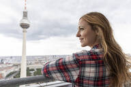 Woman enjoying a view of the city with television tower, Berlin, Germany - WPEF02303