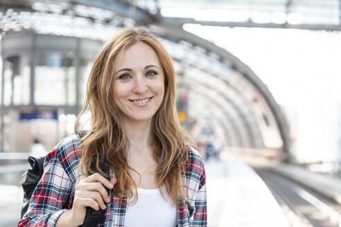 Portrait of smiling woman on the station platform, Berlin, Germany - WPEF02312