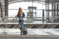 Woman with smartphone at the train station looking around, Berlin, Germany - WPEF02318