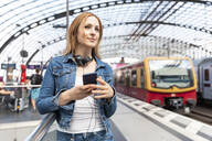 Smiling woman with smartphone and headphones on the station platform, Berlin, Germany - WPEF02321