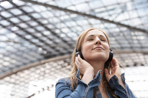 Smiling woman with closed eyes listening to music with headphones, Berlin, Germany - WPEF02327