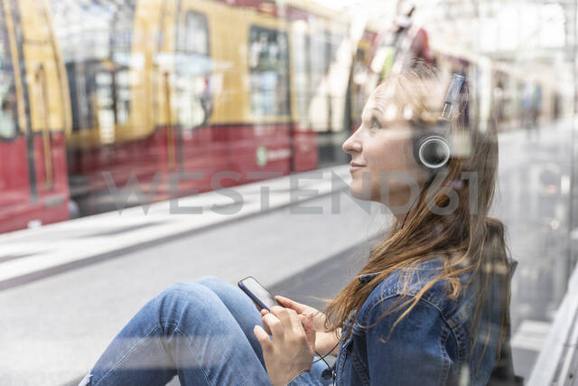 Woman with smartphone and headphones waiting at the station, Berlin, Germany - WPEF02330 - William Perugini/Westend61