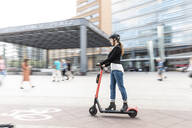Woman riding e-scooter in the city, Berlin, Germany, Berlin, Germany - WPEF02339