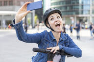 Happy woman with e-scooter taking a selfie in the city, Berlin, Germany - WPEF02351