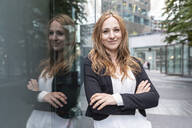Portrait of confident businesswoman leaning against a building in the city - WPEF02360