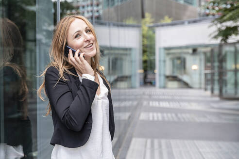 Smiling businesswoman on the phone in the city - WPEF02363