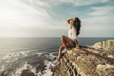 Young woman sitting on viewpoint with hand in hair, Getxo, Spain - MTBF00236