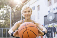 Blonde woman playing basketball in Cologne, Germany - MADF01404