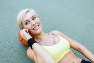 Smiling blonde woman lying on basketball and phoning - MADF01410