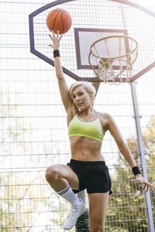 Blonde woman playing basketball, dunking - MADF01413