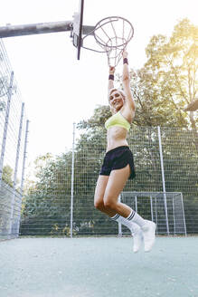 Blonde woman playing basketball, hanging on hoop - MADF01419