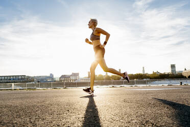 Blonde woman jogging in Cologne, Germany - MADF01425
