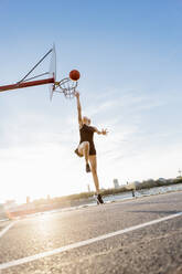 Blonde woman playing basketball in Cologne, Germany - MADF01428