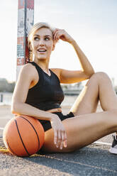 Blonde woman sitting with basketball on playing field in Cologne, Germany - MADF01431