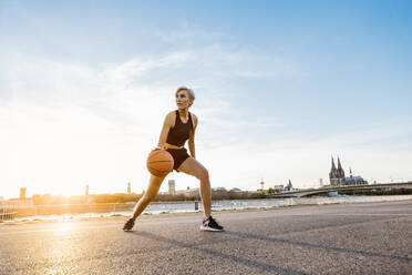 Blonde woman playing basketball in Cologne, Germany - MADF01434